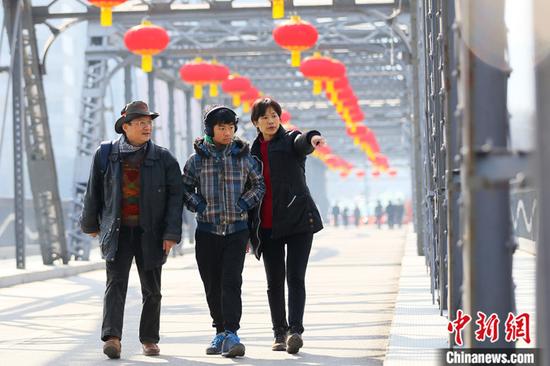 2021年春节期间,台湾商人杜书亿一家三口走过挂满火红灯笼的兰州中山铁桥。中新社记者 高展 摄