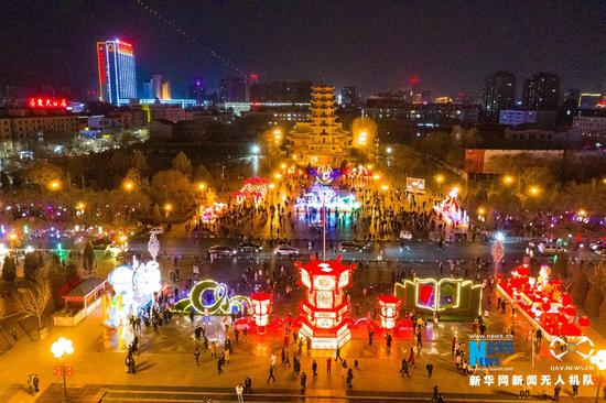 """元宵节将近,河西走廊灯光璀璨、流光溢彩,""""丝路古城""""张掖市的传统彩灯与文创光影秀交相辉映,洋溢着浓郁的节日气氛。新华网发(成林 摄)"""