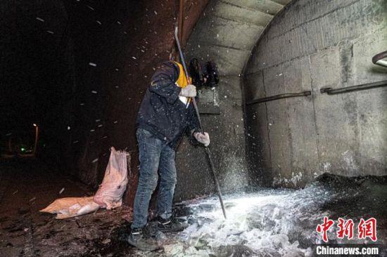 图为乌鞘岭桥隧维修工区工长苗琦举起撬棍将覆冰凿碎。 李童辉 摄