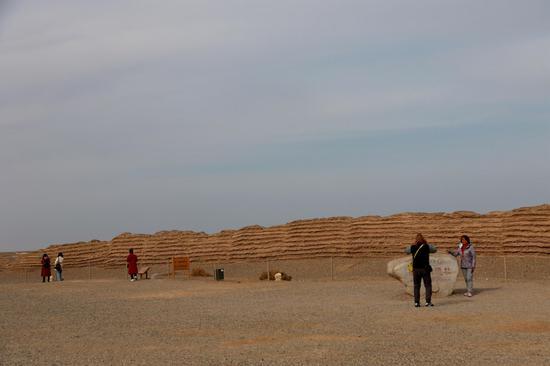 2021年2月23日,游客在敦煌市汉长城遗址参观。