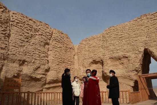 2021年2月23日,游客在敦煌市玉门关遗址参观。
