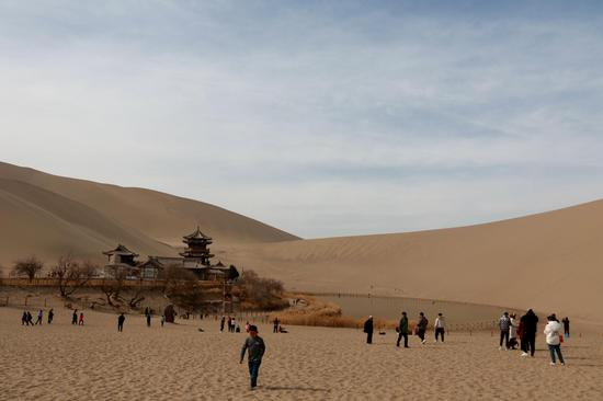 2021年2月23日,游客在敦煌市鸣沙山月牙泉景区游览。