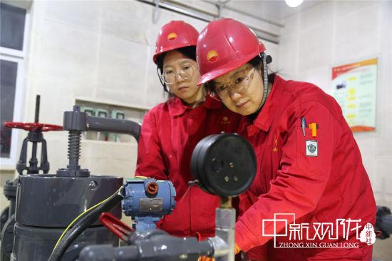 在零下19度的寒夜中,长庆油田采油十一厂方山作业区镇十二转油站,站控岗员工史华丽和权鑫在巡检。