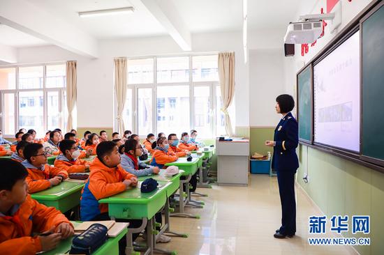 图为宣传人员给学生讲解消防安全知识。新华网发(张家纶 摄)