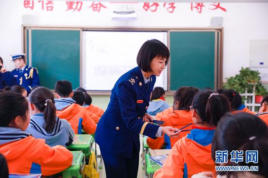 图为宣传人员给学生发放铅笔、笔袋等消防主题纪念品。新华网发(张家纶 摄)