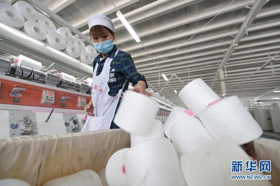 3月3日,在东乡族自治县方大丽明纺织有限公司扶贫车间,工人在涤纶缝纫线产品生产线上忙碌。新华社记者 范培珅 摄