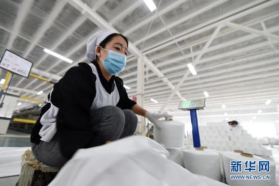 3月3日,在东乡族自治县方大丽明纺织有限公司扶贫车间,工人将涤纶缝纫线产品装袋。新华社记者 范培珅 摄