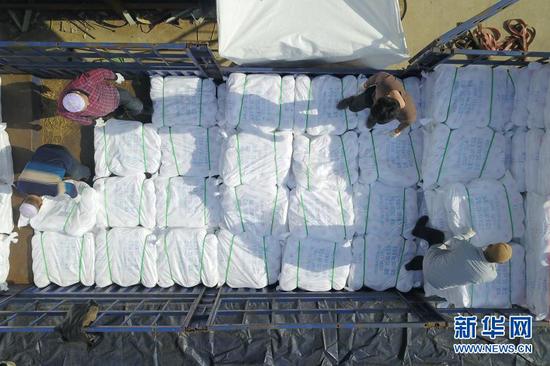 3月3日,在东乡族自治县方大丽明纺织有限公司扶贫车间,工人们将涤纶缝纫线产品装车(无人机照片)。新华社记者 范培珅 摄