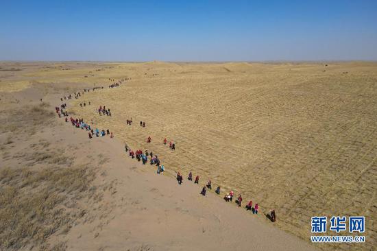 3月3日,民勤县干部群众前往沙漠腹地参加春季植树治沙活动(无人机照片)。