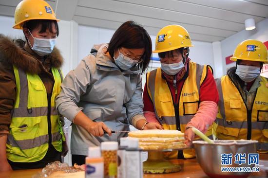 """杜萱(左二)和女工友一起在工地上制作蛋糕庆祝""""三八""""妇女节(3月4日摄)。新华社记者 陈斌 摄"""