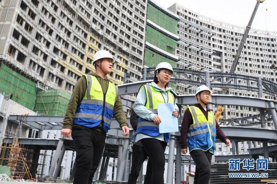 杜萱(中)带领技术人员从甘肃省妇女儿童医疗综合体项目三标段工地上走过(3月4日摄)。新华社记者 陈斌 摄