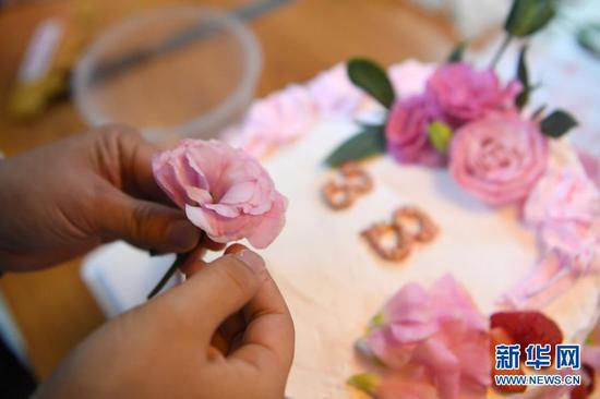 """杜萱在工地上制作蛋糕庆祝""""三八""""妇女节(3月4日摄)。新华社记者 杜哲宇 摄"""