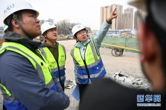 杜萱(右一)带领技术人员在甘肃省妇女儿童医疗综合体项目三标段工地上查看施工进度(3月4日摄)。新华社记者 陈斌 摄
