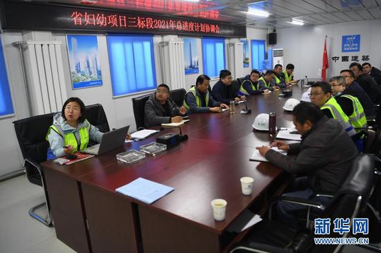 杜萱(左一)在甘肃省妇女儿童医疗综合体项目三标段项目部召开进度计划协调会(3月4日摄)。新华社记者 陈斌 摄