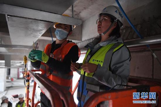 杜萱(右)在甘肃省妇女儿童医疗综合体项目三标段工地上检查指导工人作业(3月4日摄)。新华社记者 陈斌 摄