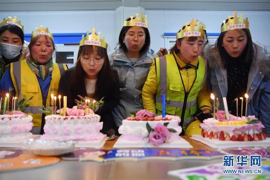 """杜萱(左四)和女工友给自己制作的蛋糕吹蜡烛庆祝""""三八""""妇女节(3月4日摄)。新华社记者 杜哲宇 摄"""