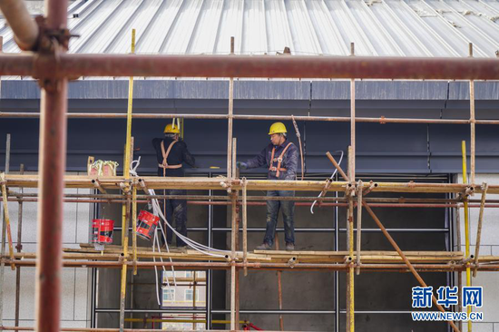 3月7日,工人在武威雷台景区文化旅游综合体项目主体建筑外墙施工。新华社记者 郎兵兵 摄