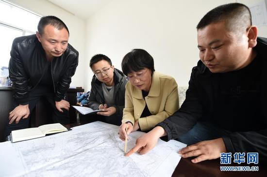 3月11日,在平凉市崆峒区林业技术工作站,张文玉(右二)和同事查看植树造林区域地形图。新华社记者 范培珅 摄