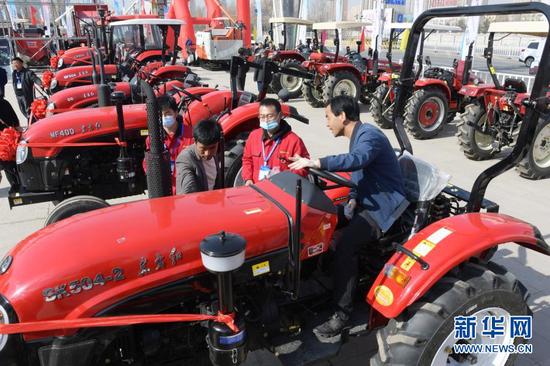 客商在临夏州举行的现代农业机械展示展销活动上选购拖拉机(3月12日摄)。新华社发(史有东 摄)