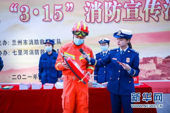 """图为在""""3•15""""消防宣传活动现场,消防员讲解如何正确使用灭火器。新华网发(张家纶摄)"""