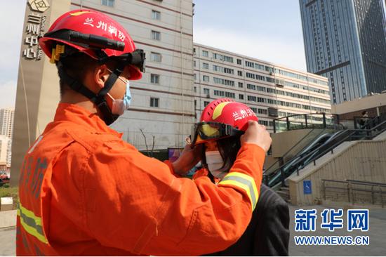 图为消防员给市民试戴消防帽。新华网发(刘欣瑜摄)