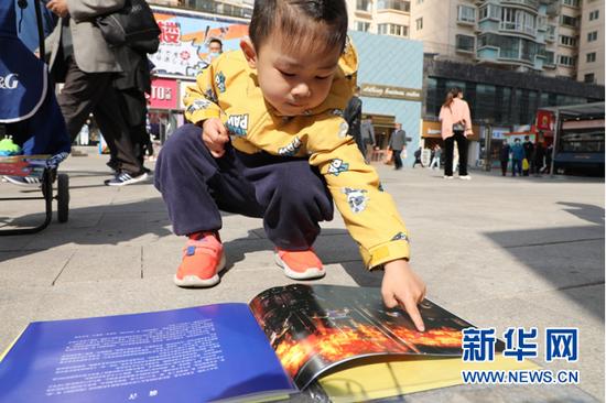 图为小朋友在活动现场阅读《漫画消防》宣传册。新华网发(刘欣瑜摄)
