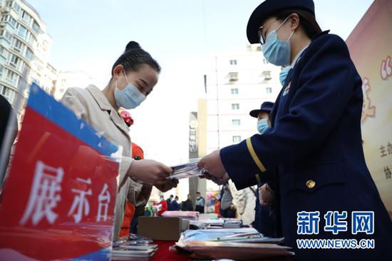 图为消防人员给市民发放宣传册。新华网发(刘欣瑜摄)