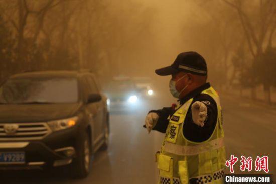 图为3月15日,甘肃多地遭遇沙尘天气,一名交警戴口罩执勤。 俞治海 摄