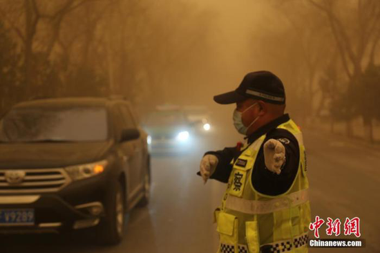 3月15日,甘肃多地遭遇沙尘天气,一名交警戴口罩执勤。 胡广信 摄