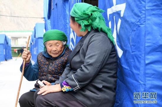 3月16日,在舟曲县果耶镇磨里村、果耶村滑坡灾害应急避险临时安置点,受灾群众在帐篷外聊天。新华社记者 范培珅 摄