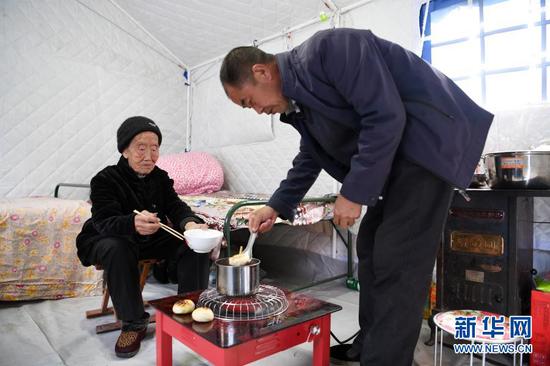 3月16日,在舟曲县果耶镇磨里村、果耶村滑坡灾害应急避险临时安置点,受灾群众在帐篷内吃饭。新华社记者 范培珅 摄