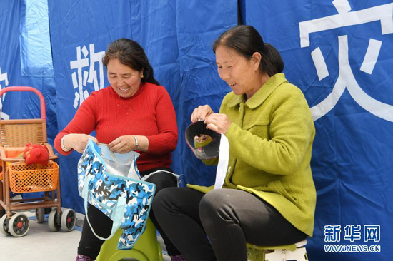 3月16日,在舟曲县果耶镇磨里村、果耶村滑坡灾害应急避险临时安置点,受灾群众在帐篷外做针线。新华社记者 范培珅 摄