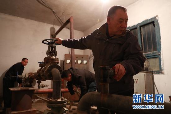 3月20日,在塘尕尔扬水站,顾正礼(右一)和同事进行启泵作业。新华社记者 杜哲宇 摄