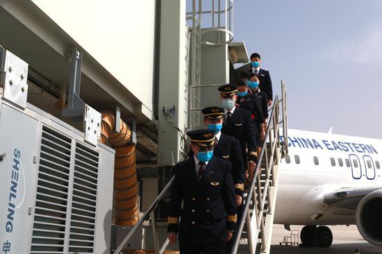 3月28日,东航武汉--银川--敦煌首航航班降落在甘肃敦煌莫高国际机场,机组人员走出机舱。