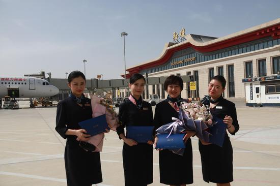 3月28日,在甘肃敦煌莫高国际机场,东航武汉--银川--敦煌首航航班机组人员在机场拍照留念。