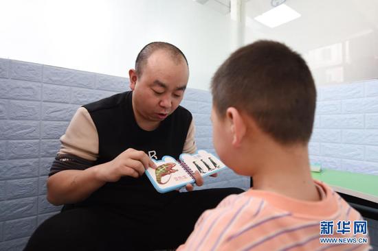 在兰州欣雨星儿童心理发展中心,丁强给孩子开展个训课程(3月29日摄)。新华社记者 范培珅 摄