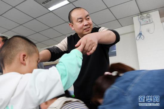 在兰州欣雨星儿童心理发展中心,丁强引导孩子进行体育运动(3月30日摄)。新华社记者 范培珅 摄