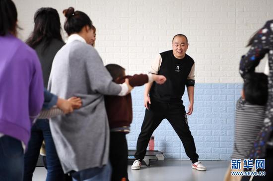 在兰州欣雨星儿童心理发展中心,丁强引导孩子和家长开展体育运动 (3月30日摄)。新华社记者 范培珅 摄