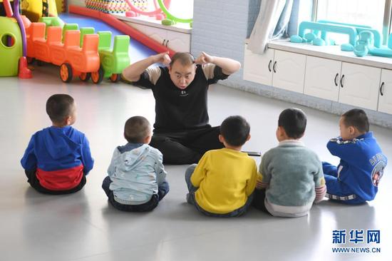 在兰州欣雨星儿童心理发展中心,丁强给孩子上游戏课 (3月29日摄)。新华社记者 范培珅 摄