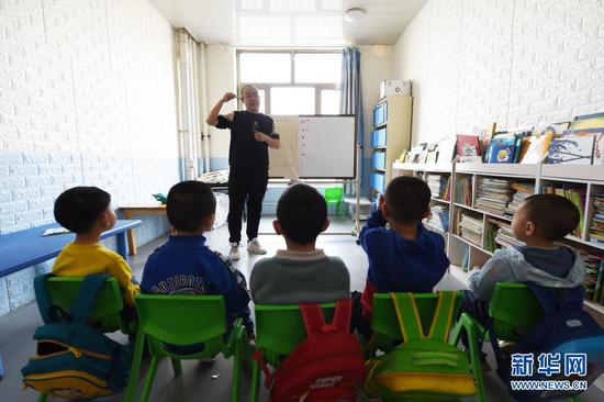 在兰州欣雨星儿童心理发展中心,丁强给孩子们上游戏课(3月29日摄)。新华社记者 范培珅 摄