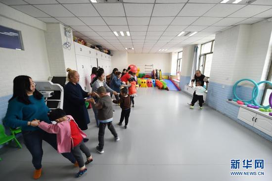 在兰州欣雨星儿童心理发展中心,丁强(右一)引导孩子和家长开展体育运动(3月30日摄)。新华社记者 范培珅 摄