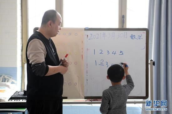 在兰州欣雨星儿童心理发展中心,丁强给孩子们上数学课(3月30日摄)。新华社记者 范培珅 摄