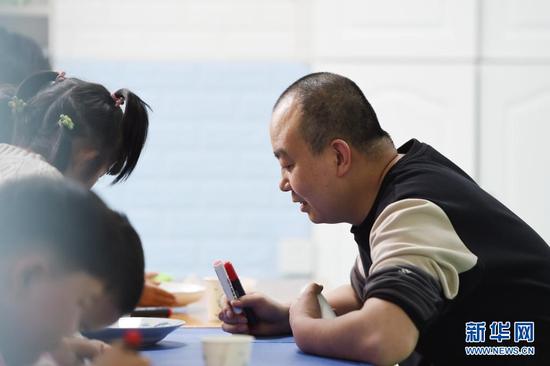 在兰州欣雨星儿童心理发展中心,丁强(右)引导孩子进行科学实验(3月30日摄)。新华社记者 范培珅 摄