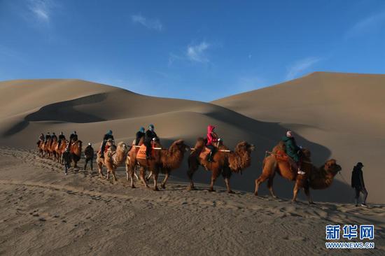 4月3日,游客在甘肃省敦煌市鸣沙山月牙泉景区游览。新华社发(张晓亮 摄)