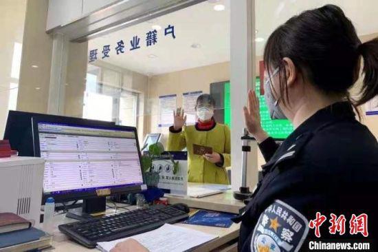 图为户籍窗口工作人员为外地迁入人员办证。(资料图)甘肃省公安厅供图