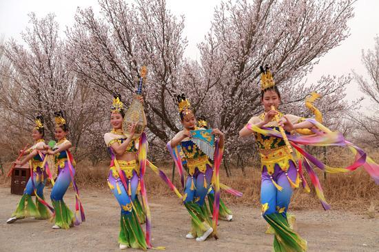 3月30日,演员在甘肃省敦煌市月牙泉镇月牙泉村的李广杏园中展示敦煌舞。