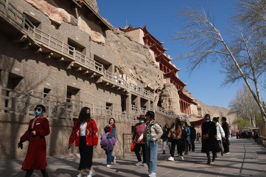 游客在甘肃省敦煌市莫高窟景区游览(2021年4月9日摄)。