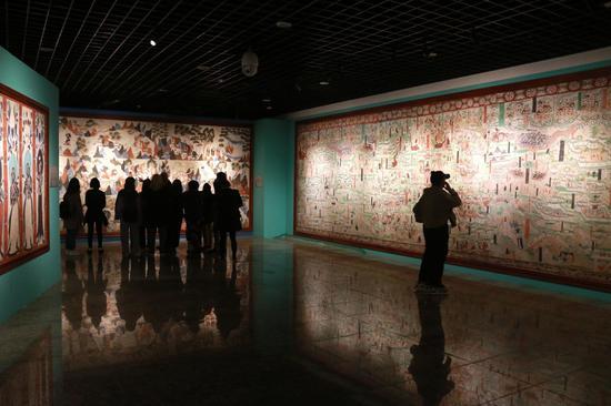 """2021年4月9日,游客在甘肃敦煌国际会展中心参观""""丝路美地""""数字敦煌展。"""