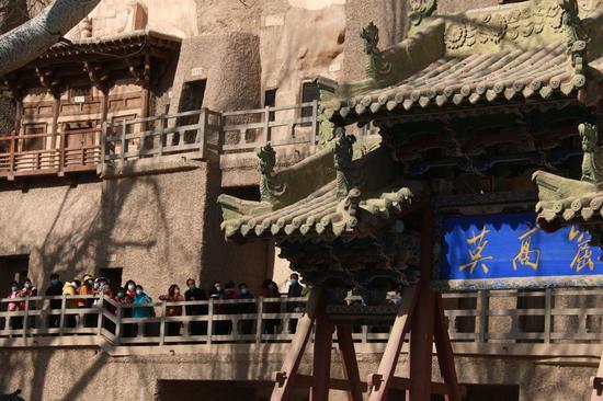 2021年4月9日,游客在世界文化遗产甘肃敦煌莫高窟景区游览。