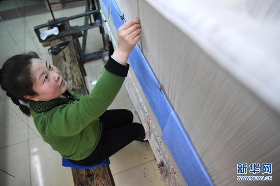 一名工人在天水丝毯织造车间里编织丝毯(4月12日摄)。新华社记者 杜哲宇 摄
